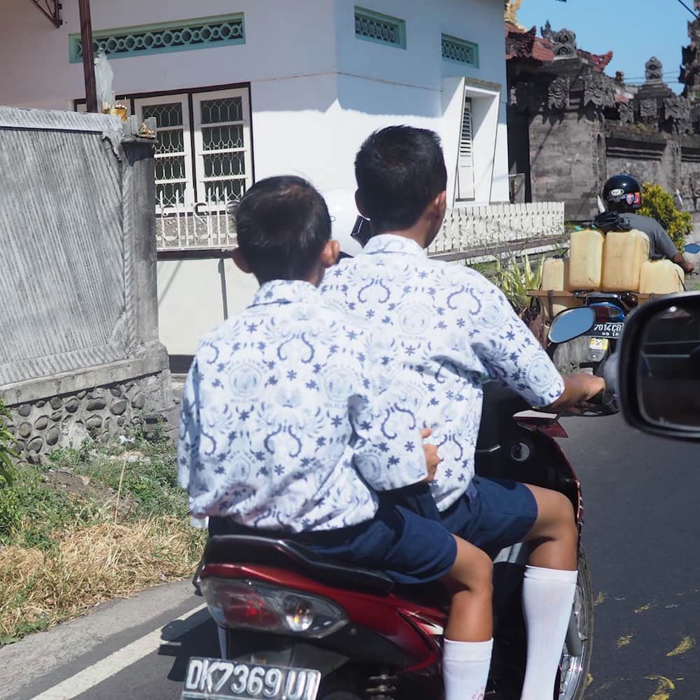 Two schoolkids in uniform on their to school on their scooter