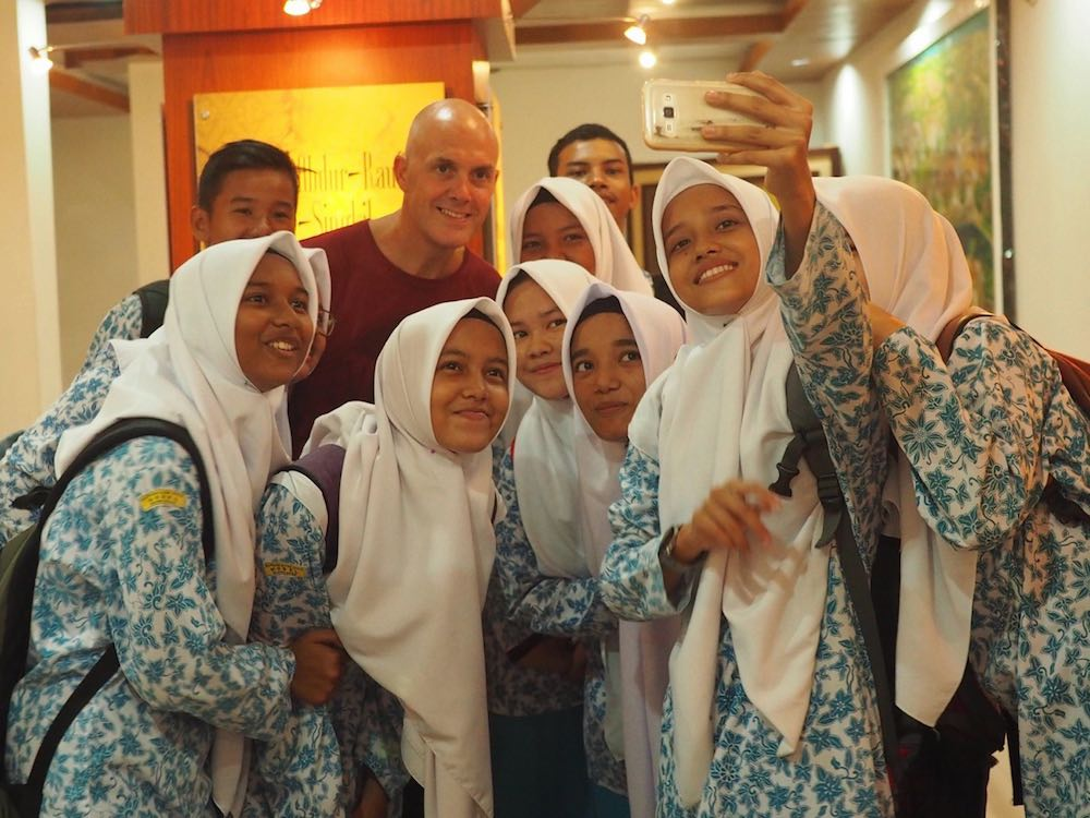 Ian having a photograph taken with a group of students Inside the Banda Aceh Museum