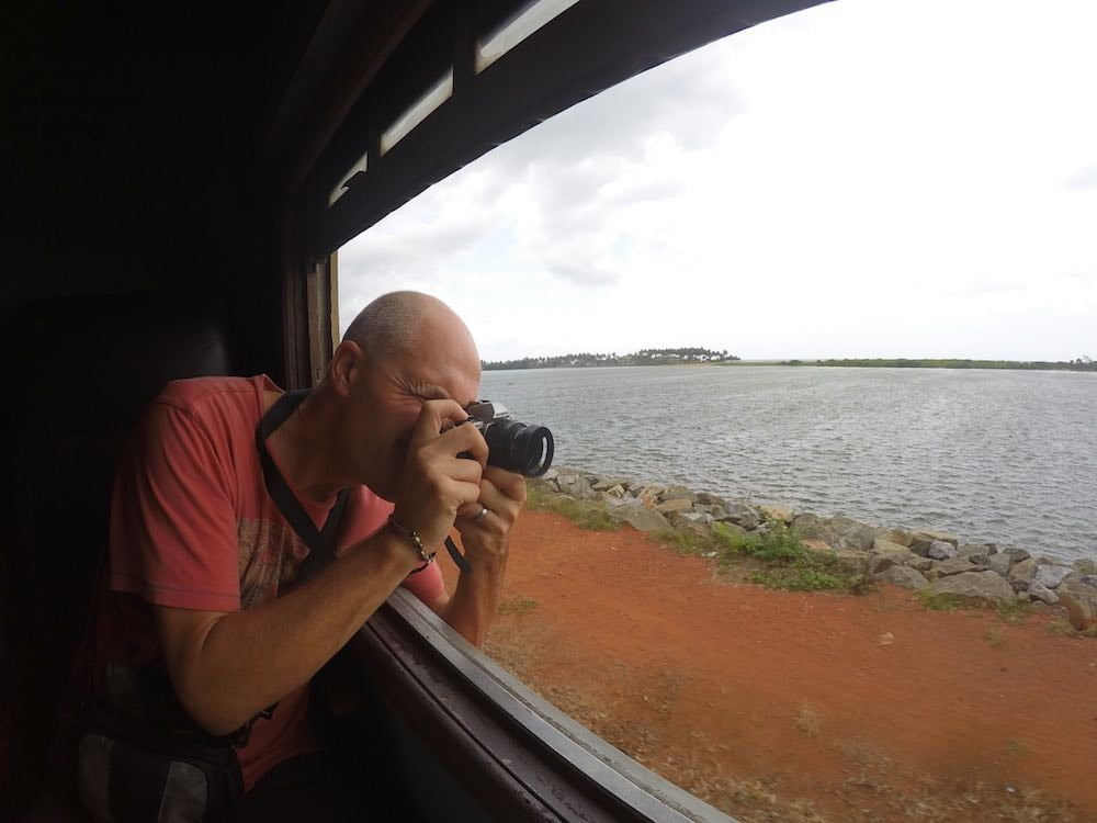 Ian taking a photograph out of a window on the train from Colombo to Galle