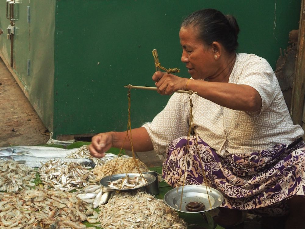 A woman weighs fish in the local market