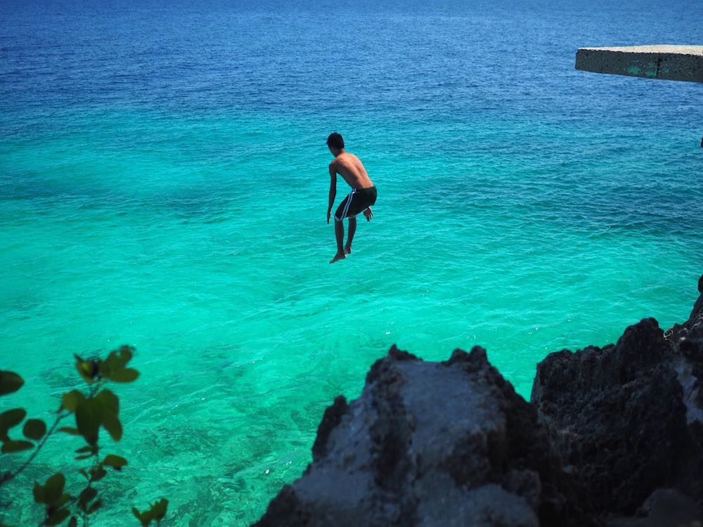 A boy Jumping off a cliff at Salagdoong Beach