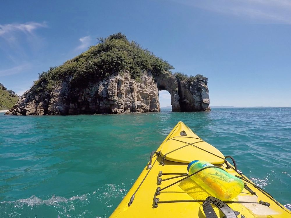 Heading towards a natural arch while kayaking in Golden Bay
