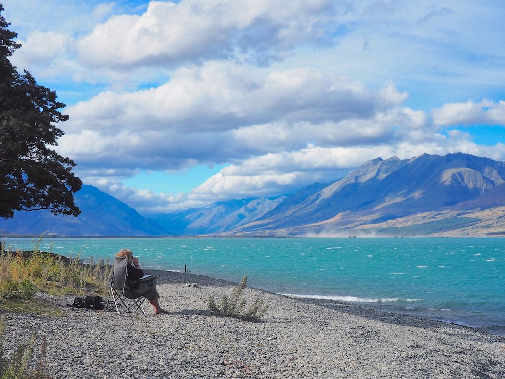 Nicky sitting in a camp chair on Lake Ohau beach