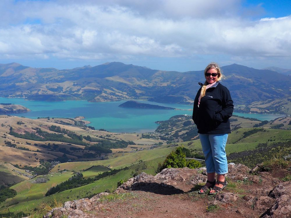 Nicky standing next to a view of Akaroa
