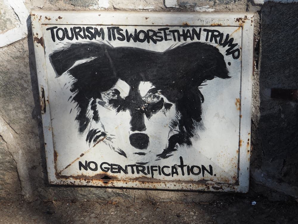 """Sign which says """"Tourism is worse than Trump - no gentrification"""""""