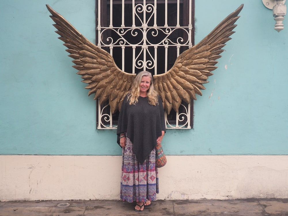 Nicky standing in front of a pair of brass wings, Barranco