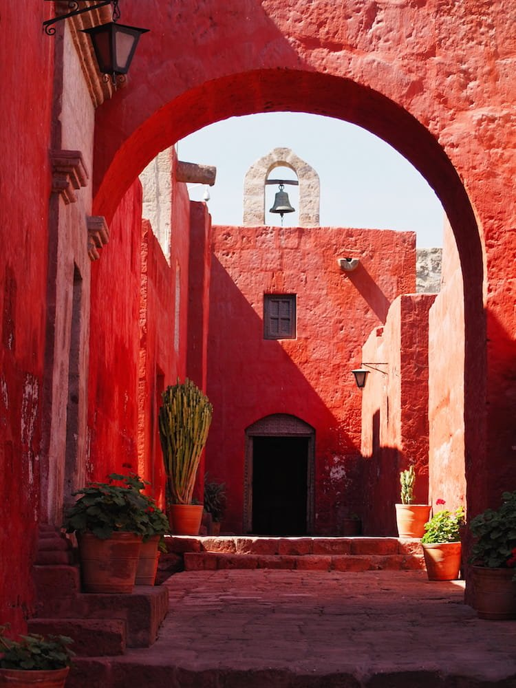 A red arch leading to a red wall