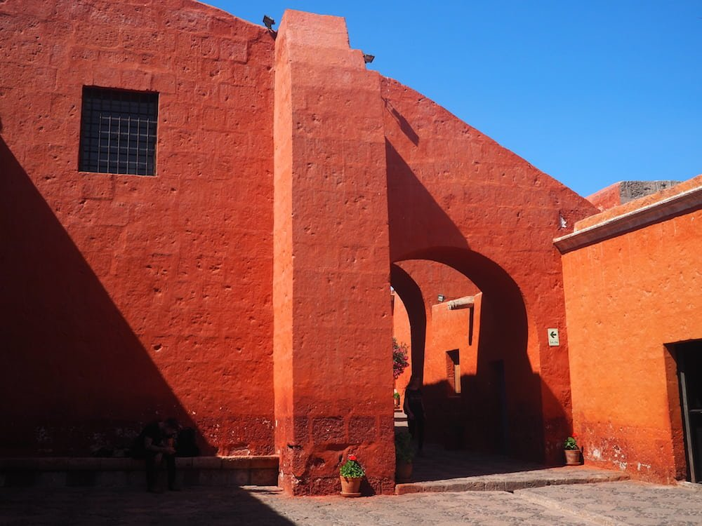 A red wall against a blue sky