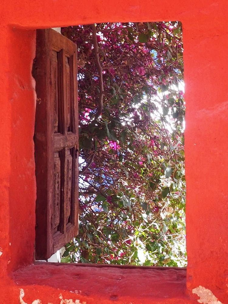 An open window on a red wall