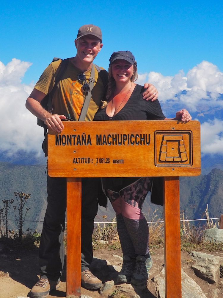 Ian and Nicky pose behind the sign at the summit of Machu Picchu Mountain