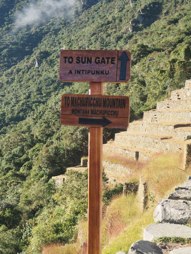Signpost pointing to the Sun Gate and Machu Picchu Mountain