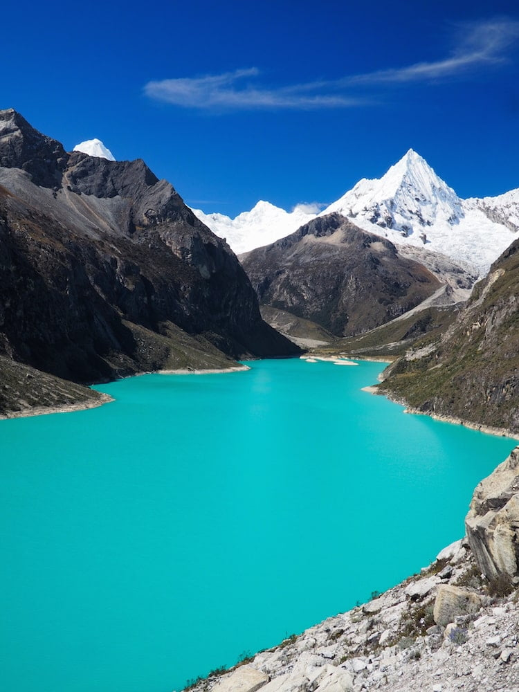 Turquoise lake in the foreground, snowy mountains in the background