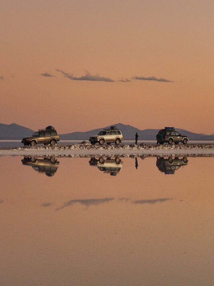Jeeps parked at the Salar de Uyuni at sunset