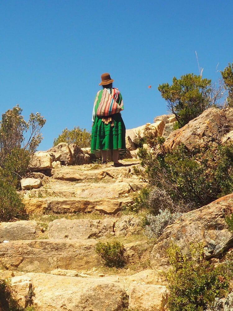 A cholita in traditional dress climbing to Cerro Queñuani