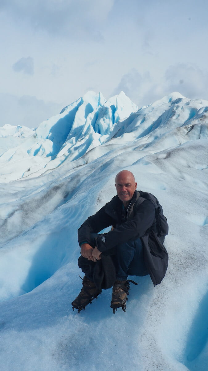 Ian sitting down on the glacier