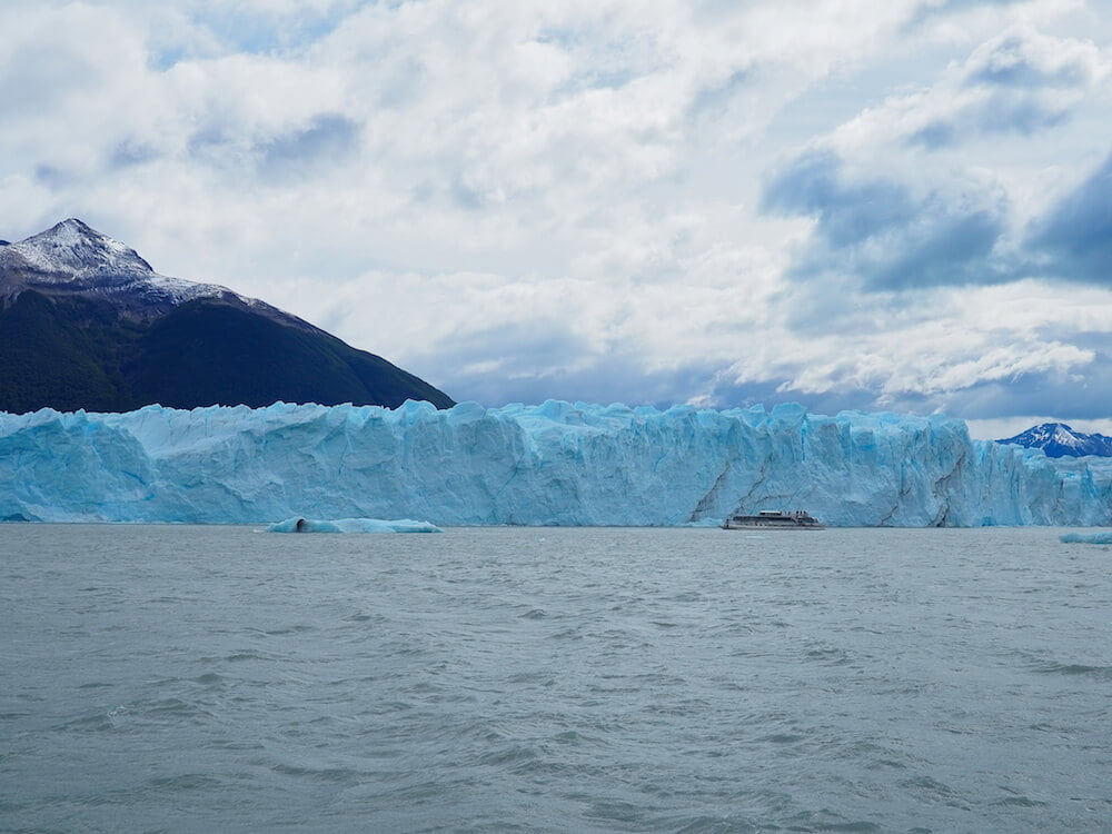 A tour boat passes close to the glacier wall