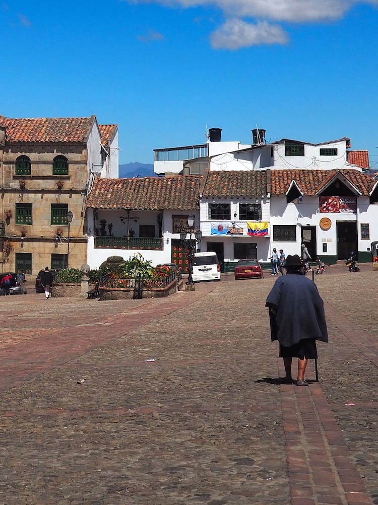 An elderly lady crossing the main square