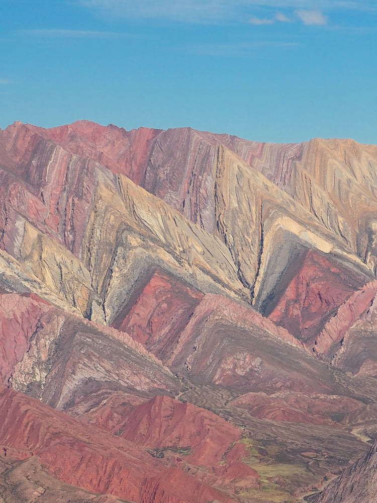 Mountainside with pink, cream and grey colourings in the shape of sharks' teeth