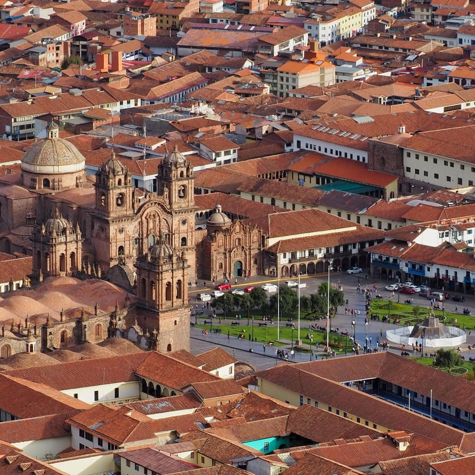 Arial view of red-roofed buildings, a cathedral and a plaza