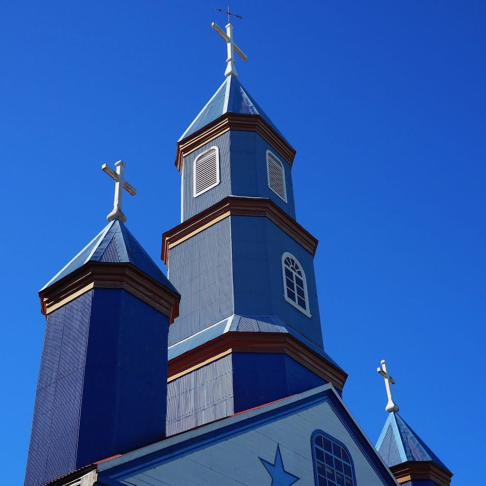 Blue wooden spires of a church against a blue sky