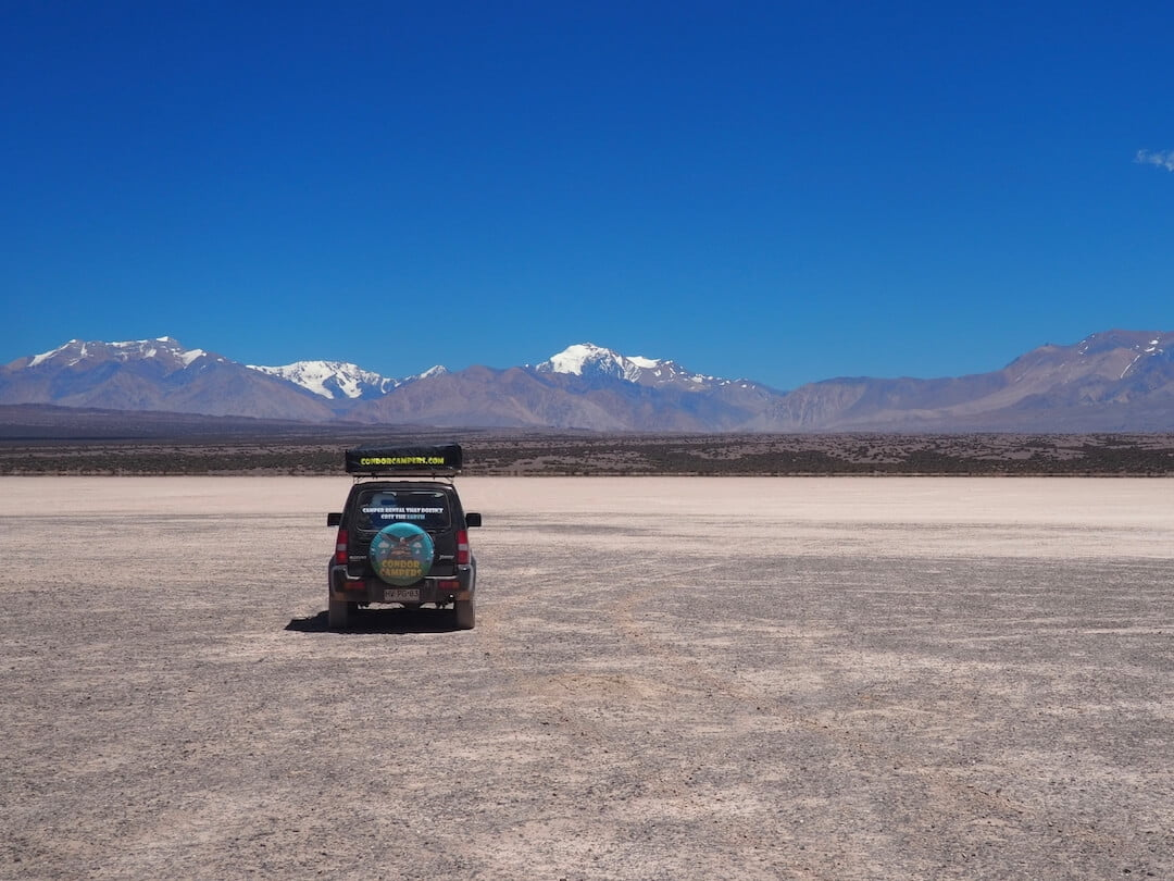 A jeep is parked on a dried mudflat with mountains in the distance and a blue sky