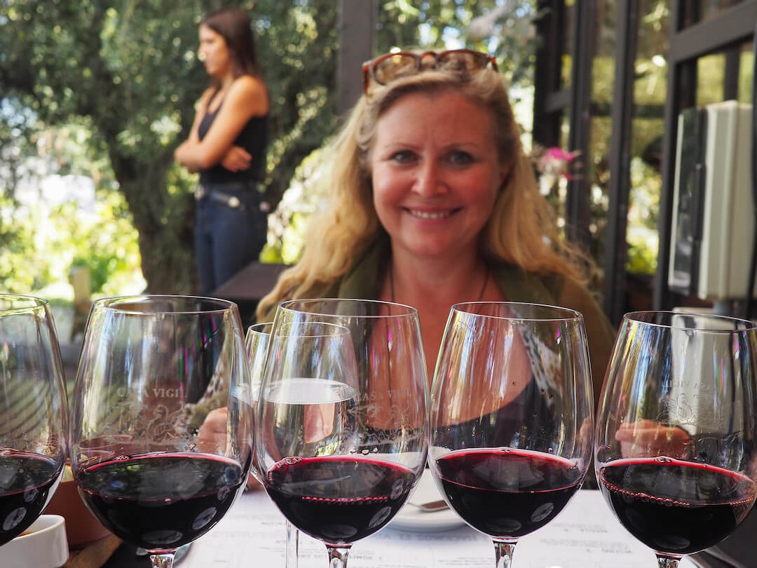 Tasting glasses of red wine in the foreground and a smiling woman in the background