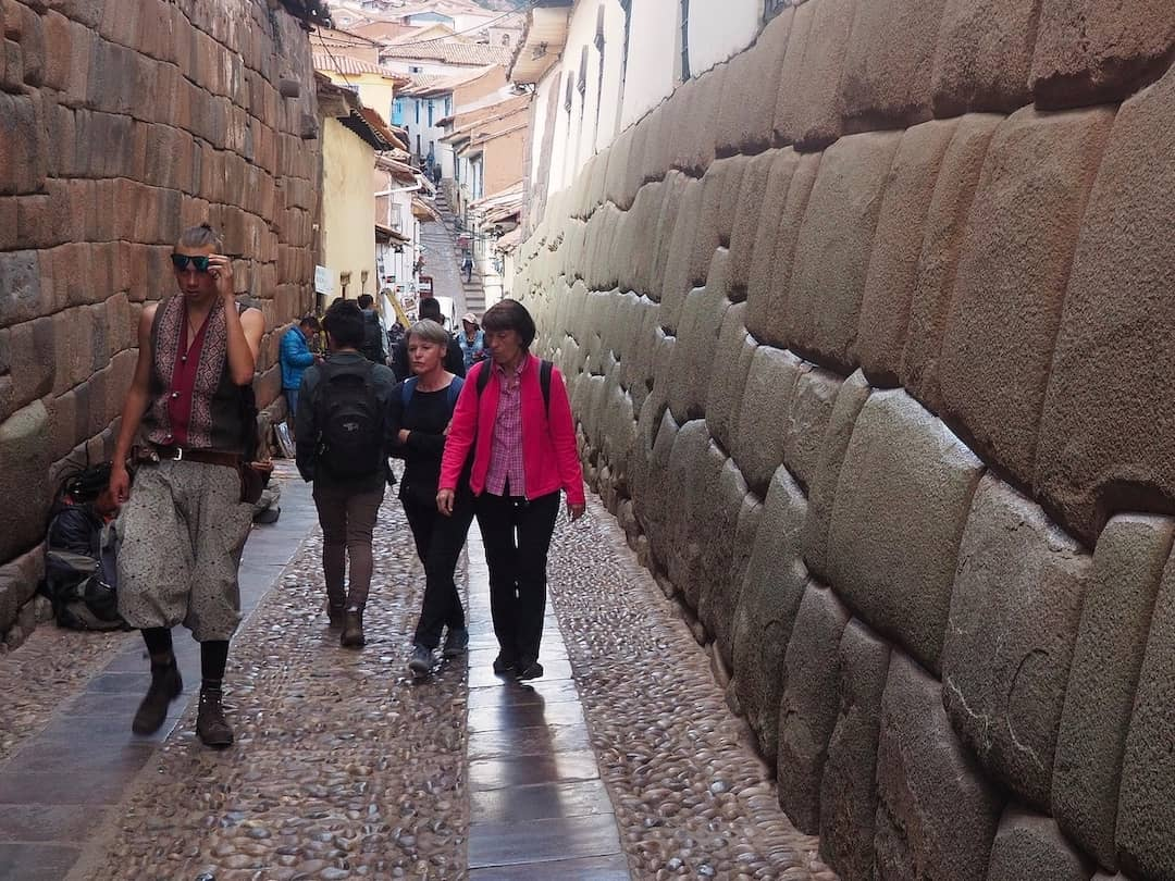 People walking in a narrow street with a large stone wall on the right