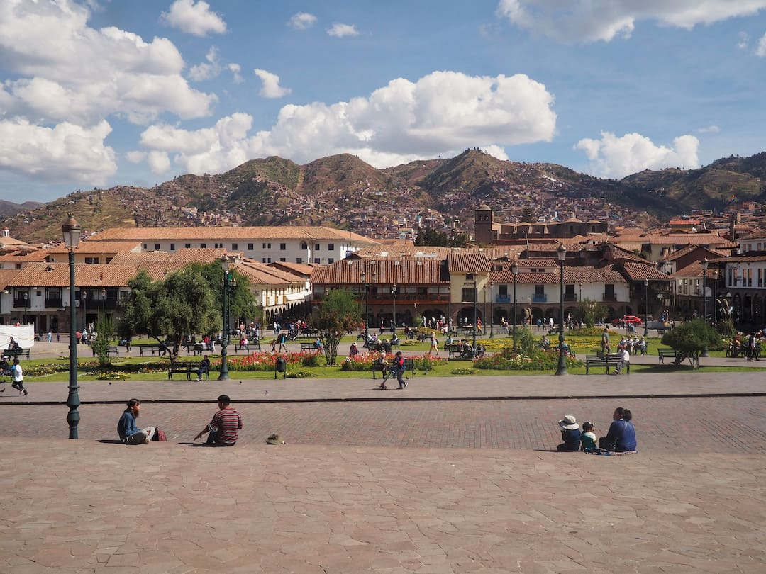 People sitting on stone steps in front of a square with buildings and mountains in the background