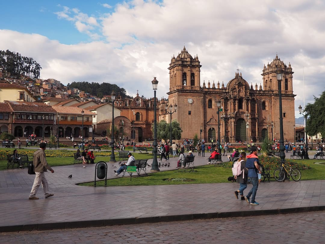 People walking along a plaza with a cathedral in the background