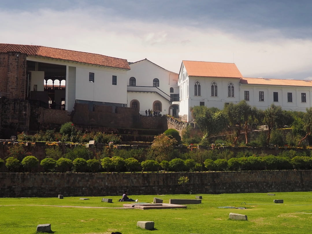 A grassy area in the foreground and a white building with red roof in the background