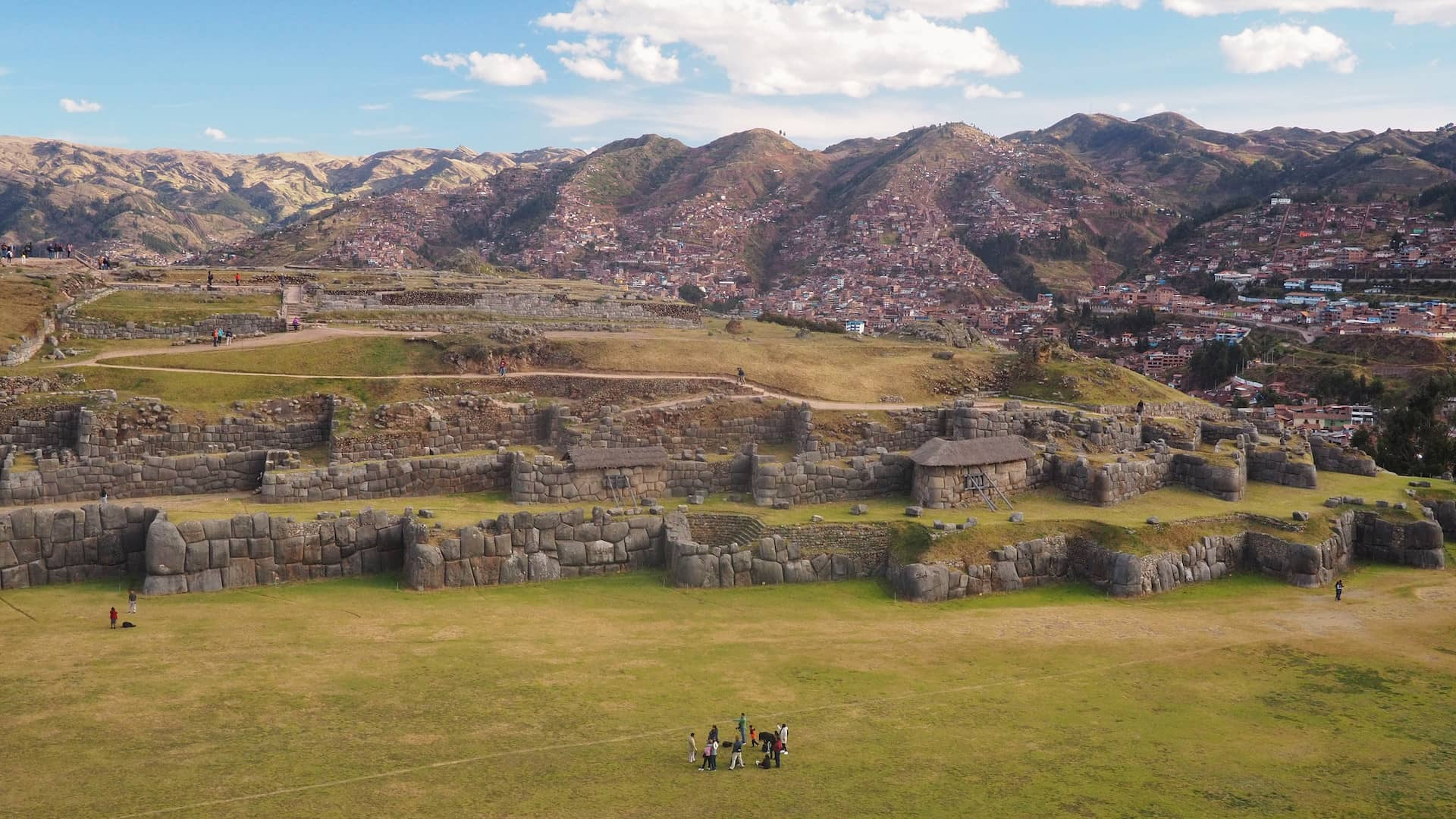 A panoramic view of ruined stone walls with red roofed houses and mountains in the background