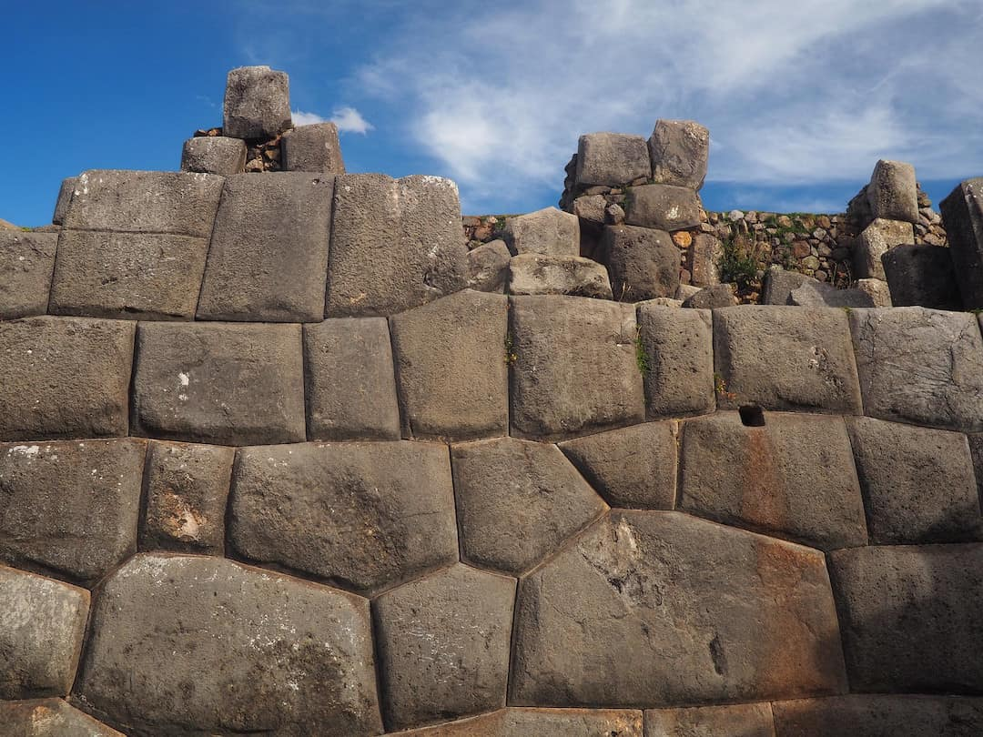 A wall constructed with irregularly shaped stones under a blue sky