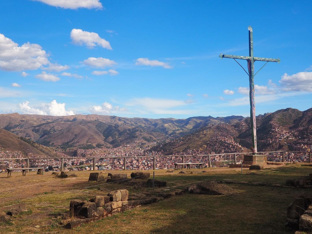 A wooden cross standing on a grassy area overlooking red roofed houses below