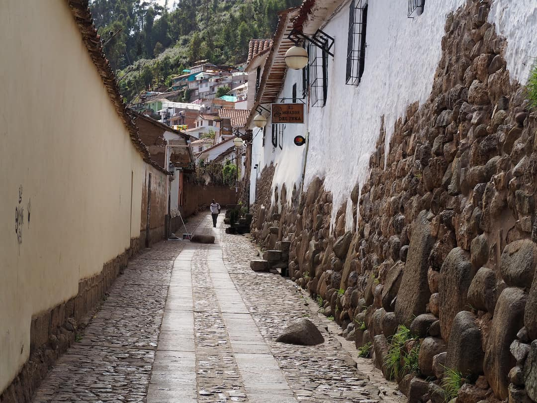 A narrow cobbled street with a long white-washed wall on the right half-covered in stone