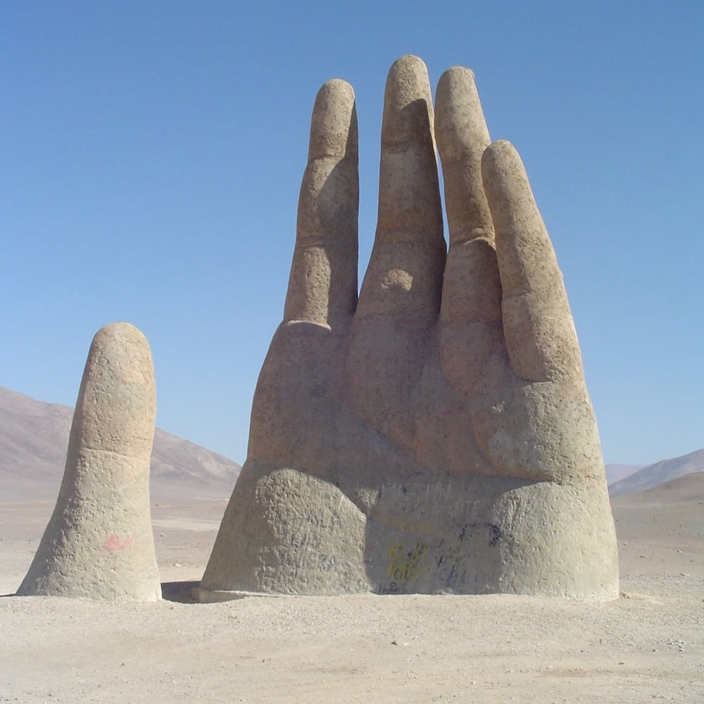 A large sculpture of a hand emerges from the desert sand