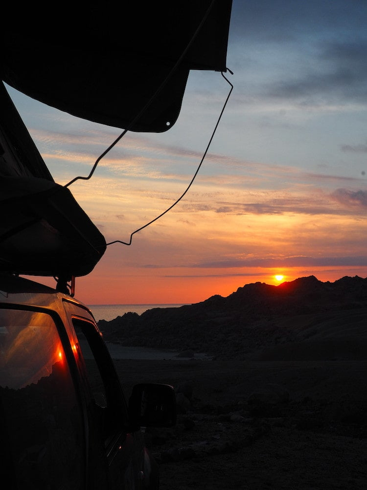 Side view of a car and rooftop tent in the foreground and a sunset in the background