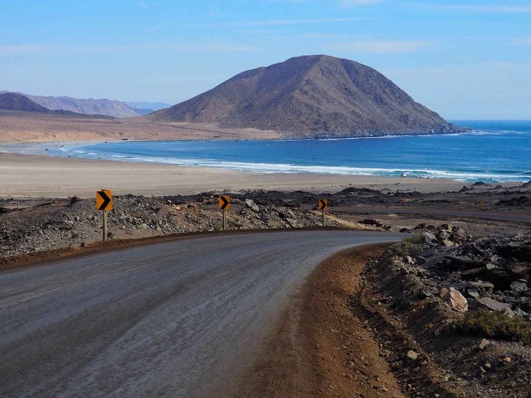 """A road leads to a beach with a """"sugar loaf"""" hill in the background"""
