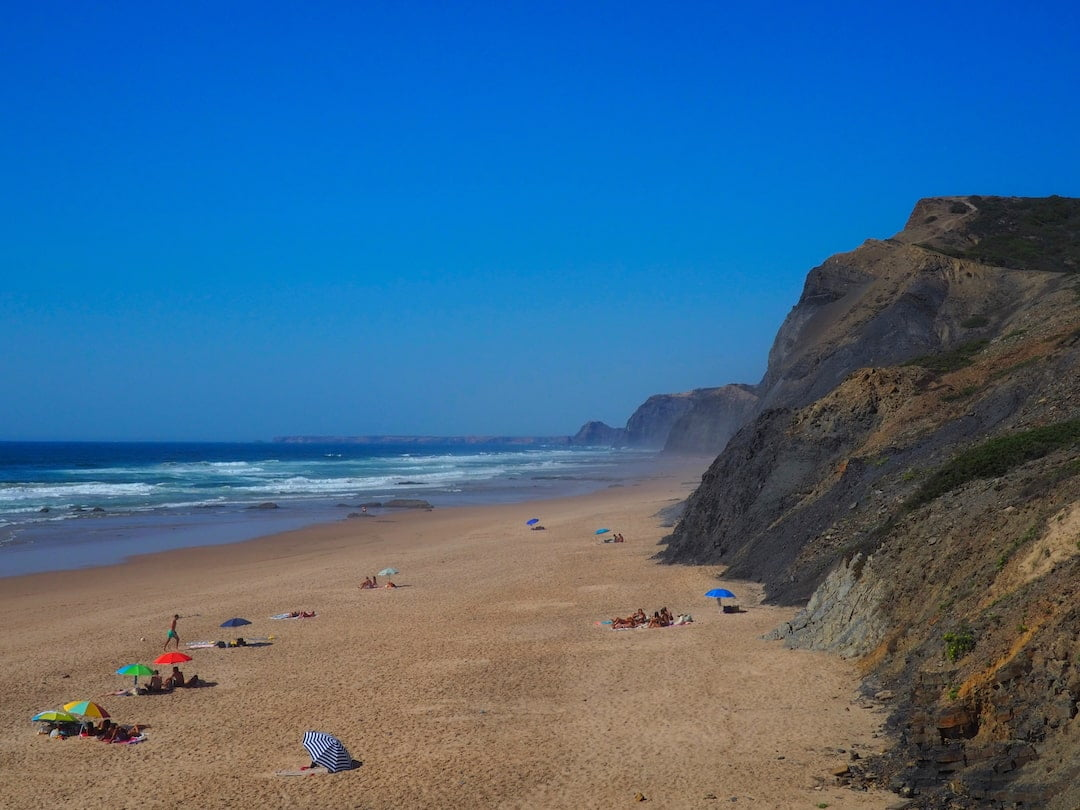 Sandy beach below cliffs with umbrellas and sunbathers
