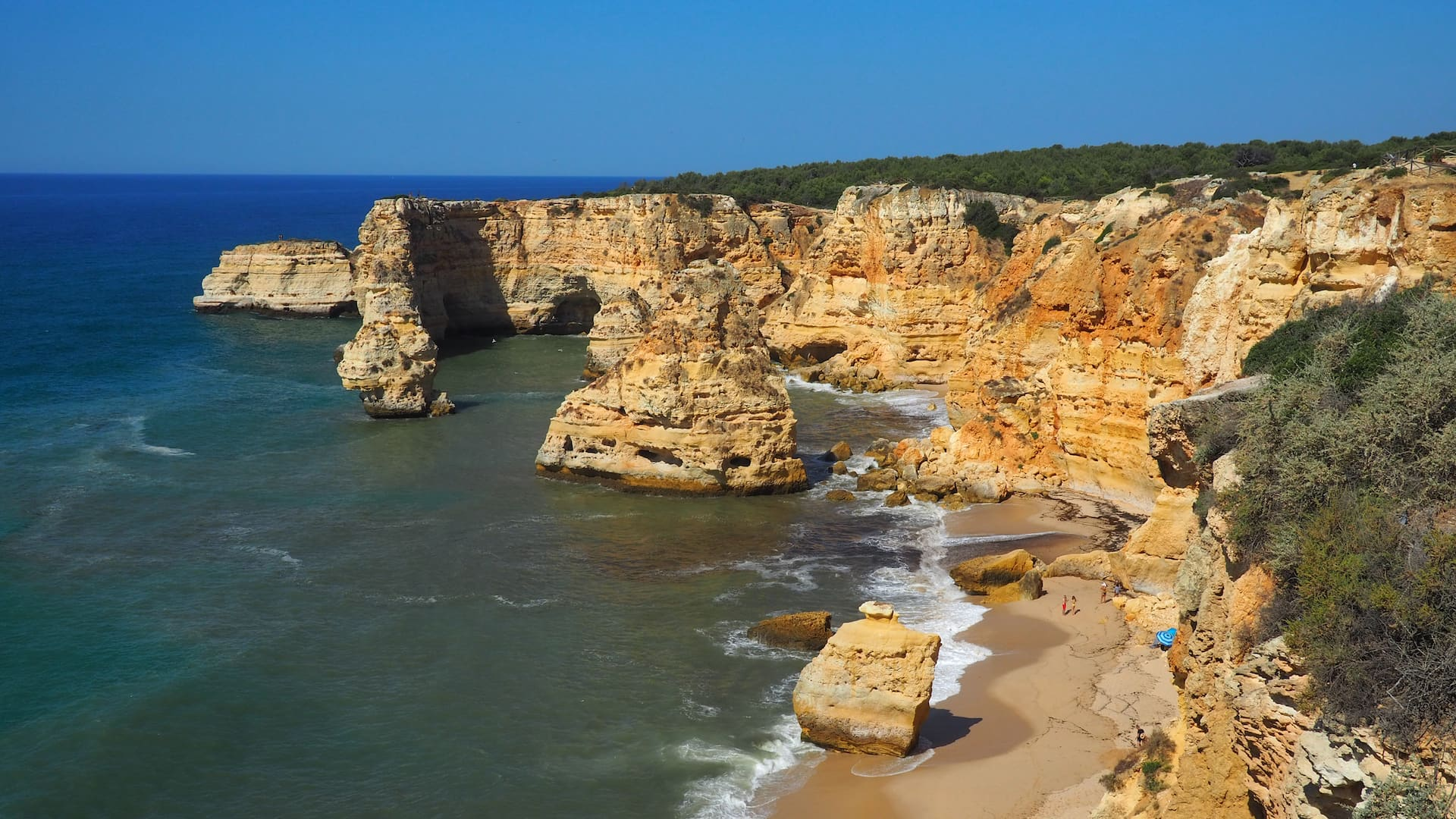 A golden sand beach surrounded by sandstone cliffs and large rocks just offshore