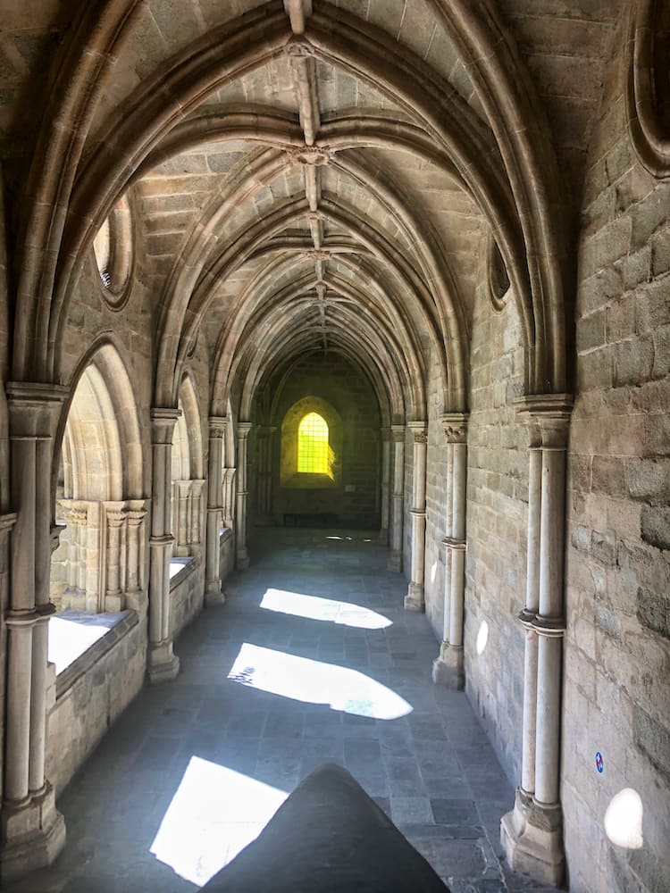 And old stone arched passageway with a yellow tinted oval window in the background