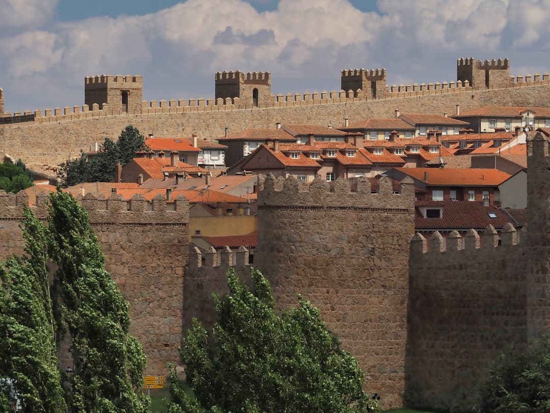 A wall with turrets surrounding red-roofed buildings
