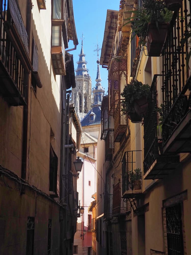 A narrow street with a cathedral spire in the background