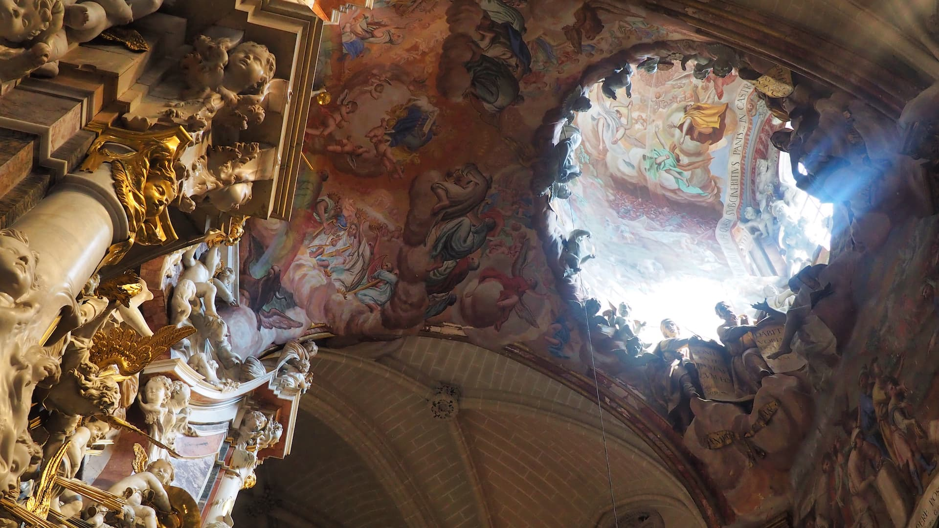 A ceiling fresco painting is illuminated by light shining through a dome above