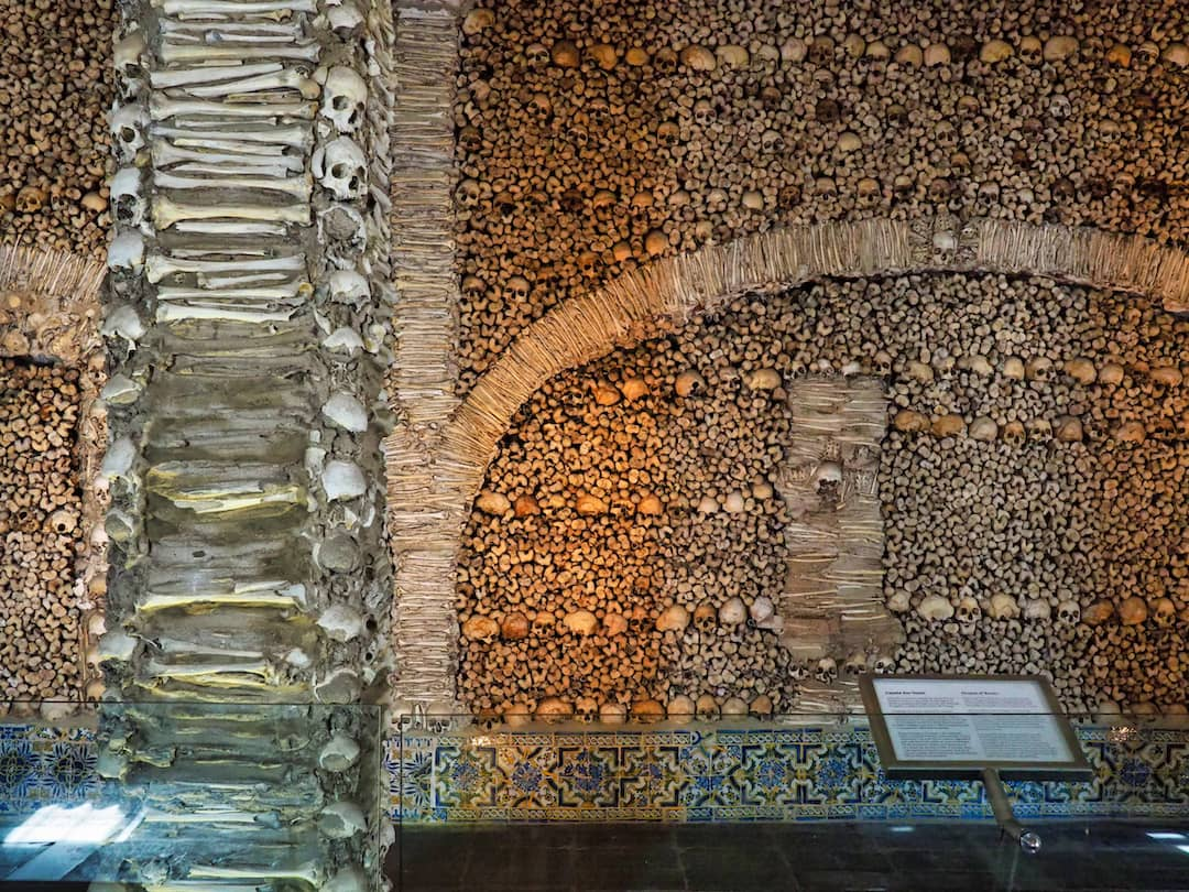 """A pillar """"decorated"""" with bones stands in front of a wall of bones"""