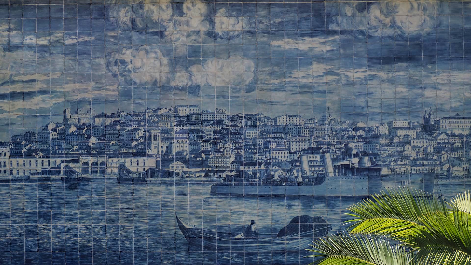 A vintage depiction of Lisbon on a collage of blue tiles with green leaves to the bottom right