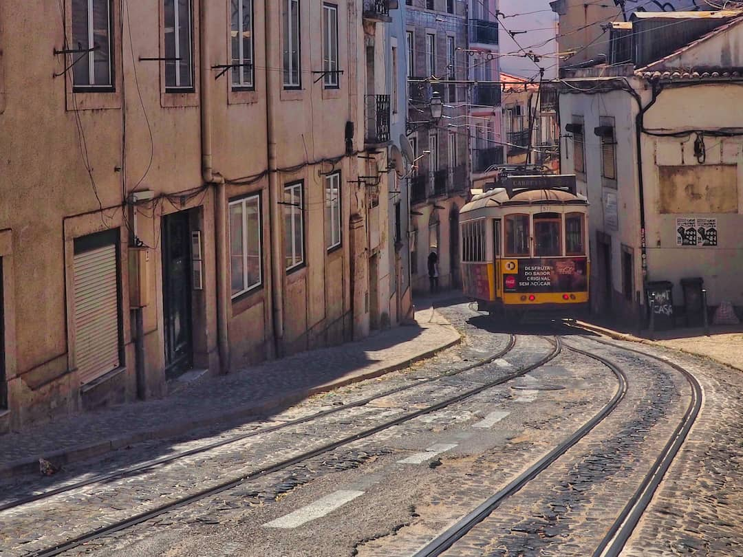 A tram emerges from a narrow street