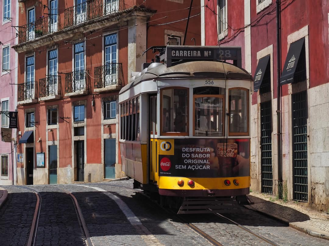 A yellow tram approaches within a street of red buildings