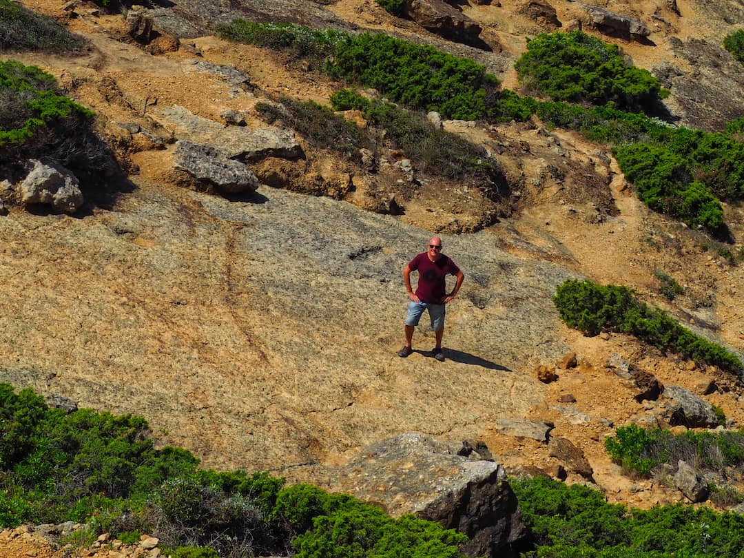 Ian looks up from a rocky area surrounded by impressions in the ground (dinosaur footprints)