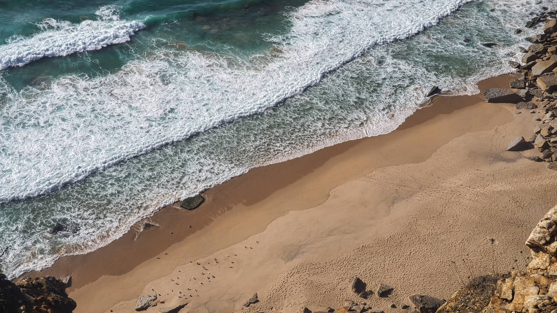 Aerial view of waves crashing on to a golden beach