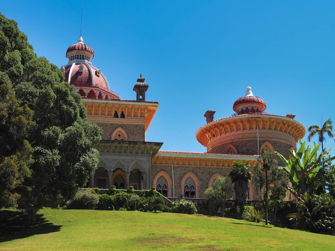 A garden leads to a brightly coloured palace with orange walls and a pink dome
